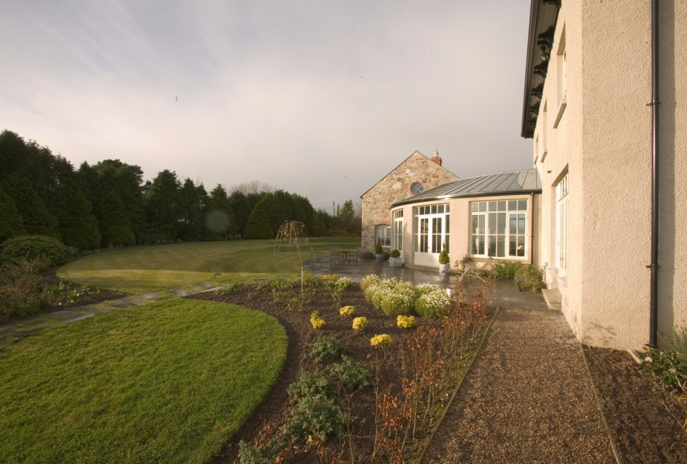 Lime render finish provides a soft natural tone to this new country house set on top of a drumlin